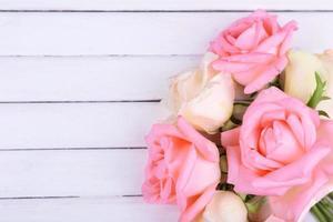 lindas rosas sobre fundo branco de madeira foto