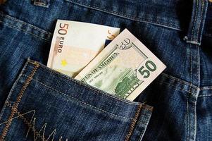 notas de euro e dólar no bolso da calça jeans foto