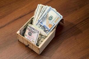caixa com notas de dólar em fundo de madeira foto
