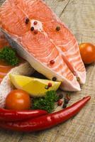 salmão cru, legumes e especiarias em uma mesa de madeira velha