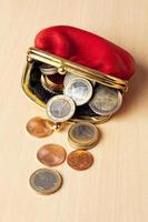 bolsa vermelha cheia de moedas de euro foto