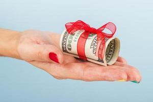 mão de mulher com dinheiro no fundo azul foto
