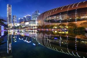 marco moderno iluminado e skyline na margem do rio