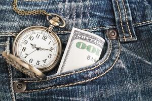 relógio de bolso e uma nota de dólar em jeans azul foto