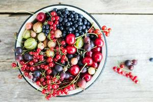diferentes frutas frescas em uma panela no fundo de madeira foto