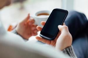homem usando telefone celular e segurando uma xícara de chá foto