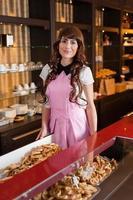feliz sorridente jovem vendedor em uma loja de bolos