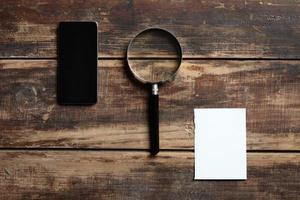 telefone celular, magnefier e folha de papel na mesa de madeira foto