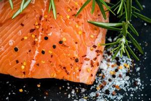 filetes de salmão cru com ervas aromáticas e azeite foto