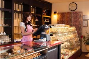 feliz sorridente jovem vendedor em uma loja de bolos foto