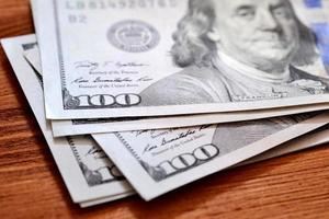 notas de dólares americanos na mesa de madeira foto