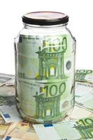 frasco de vidro e notas de euro foto