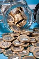 moedas de euro derramando do pote foto