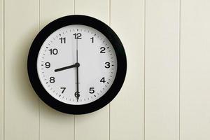 relógio na parede do painel de madeira pintada foto