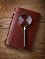 notebook com uma lupa na mesa de madeira foto