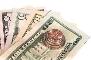 várias pilhas de moedas americanas com algumas notas de dólar.