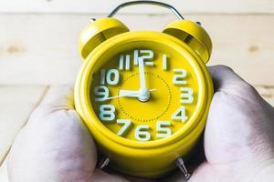 mão segure o despertador amarelo sobre fundo de madeira foto