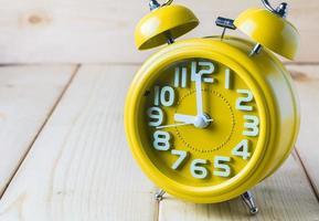despertador amarelo sobre fundo madeira foto