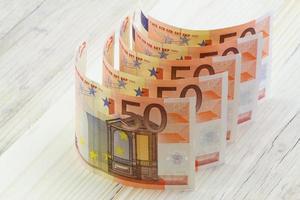 notas de euro em uma linha na superfície de madeira foto