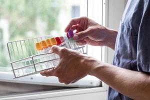 uma enfermeira vista segurando frascos no consultório médico foto