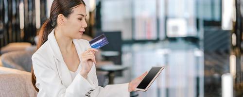 uma mulher asiática usando cartão de crédito para compras on-line no lobby