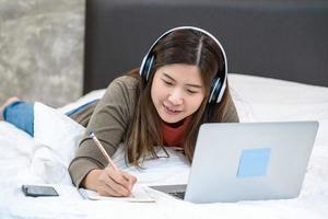 jovem mulher asiática usando laptop e escrevendo em casa foto