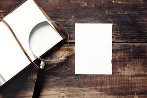 caderno, folha de papel e lupa em uma mesa de madeira foto