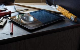 tablet em um armário escuro, rodeado por ferramentas foto