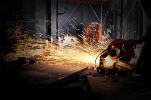 trabalhador cortar metal com moedor. faíscas ao moer ferro foto