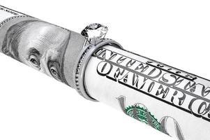 nota de cem dólares em um anel de casamento de diamante foto