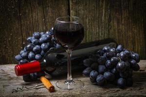 garrafa de vinho tinto, uva e saca-rolhas na mesa de madeira