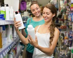 mulher selecionando shampoo na loja foto