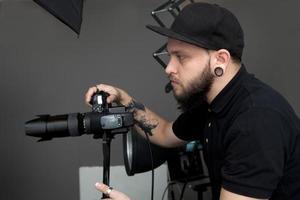 fotógrafo tirando fotos no estúdio com paredes cinza