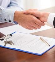 cliente, apertando a mão do corretor de imóveis depois de assinar um contrato