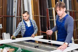dois trabalhadores escolhendo o perfil da janela de pvc foto
