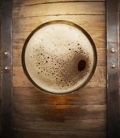 barril de cerveja com vidro no fundo da mesa de madeira foto