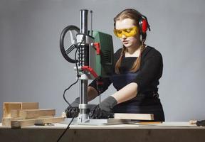 carpinteiro feminino e máquina de perfuração. foto