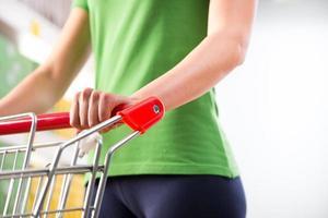 mulher com carrinho no supermercado foto