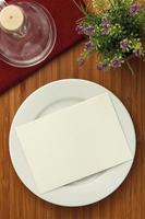 chapa branca e flor na mesa de madeira foto