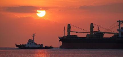 navio de carga e belo pôr do sol no oceano foto