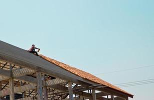 trabalhador no telhado em trabalhos de aparafusar foto