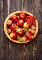 maçãs e nozes em uma tigela de madeira foto