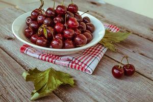 cerejas maduras frescas em uma placa de madeira escura. foto