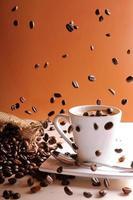 grãos de café caindo na mesa com uma xícara de café foto