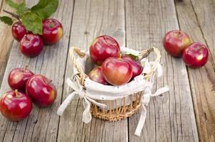 cesta com maçãs em uma mesa de madeira foto