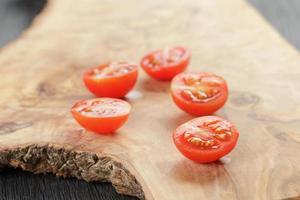 corte ao meio tomate cereja com folhas de manjericão na mesa foto