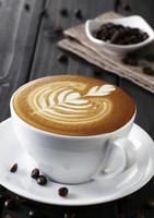 xícara de café e Pires em uma mesa de madeira. fundo escuro foto
