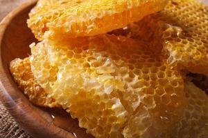 favo de mel dourado fresco na macro placa de madeira. horizontal