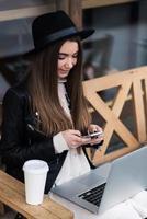 menina escrevendo texto no telefone celular durante o trabalho no net-book foto