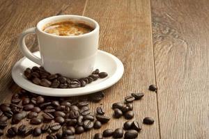 xícara de café e Pires em uma mesa de madeira foto